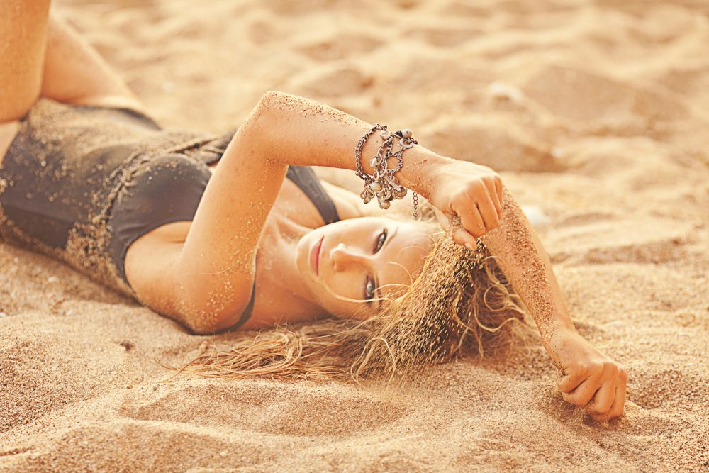 beautiful girl in a black bathing suit lying on the sand